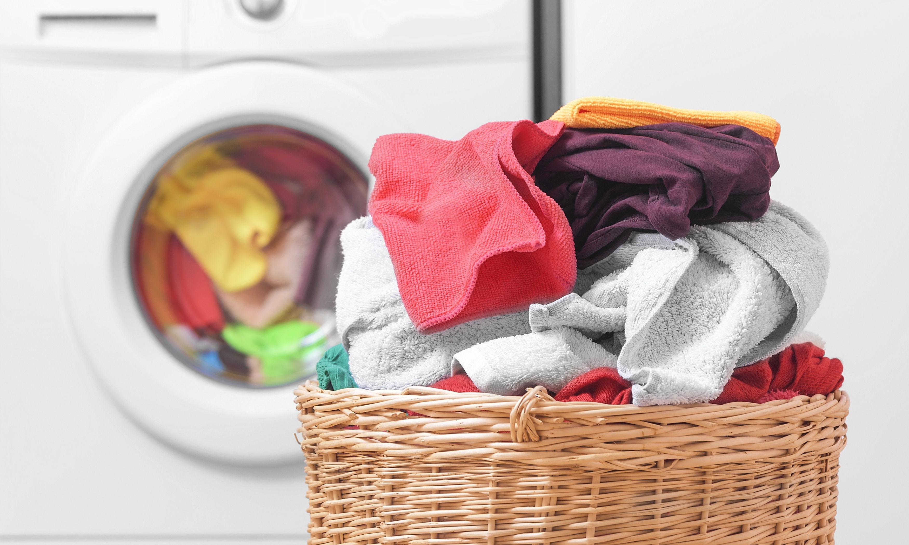 Basket full of laundry with washing machine in the background