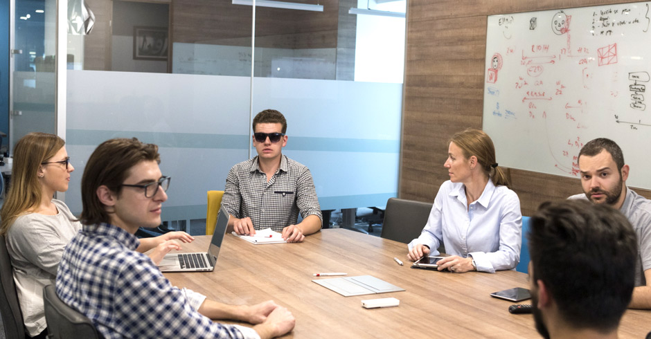 Image of a blind person participating in a business meeting around a conference table in an office setting with people making notes on paper and laptops and tablets