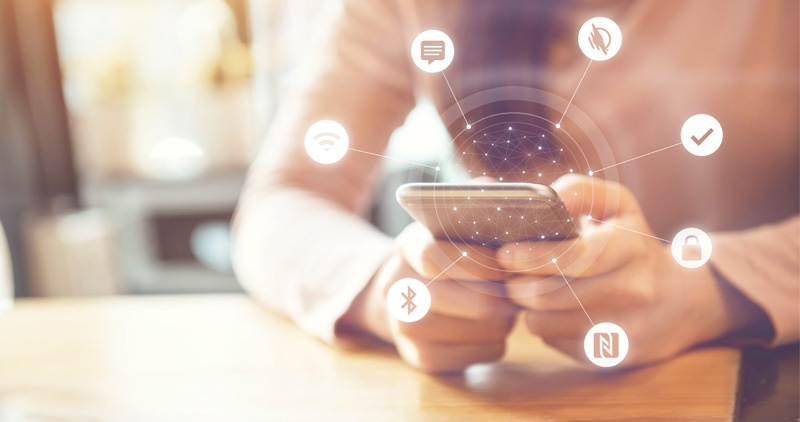 Woman holding smartphone with icons radiating out from the device. Icons show symbols for bluetooth, messaging app, WayAround, and more