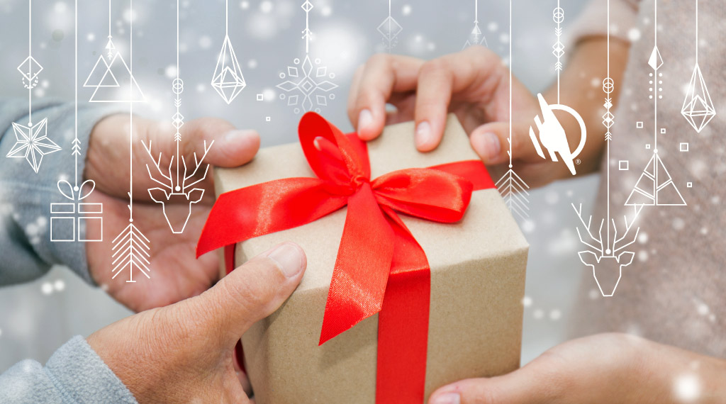 Older persons hands on a wrapped Christmas package with red ribbon giving gift to younger person with their hands receiving the package. White outlines of various hanging ornament graphics on layer above gift giving image.