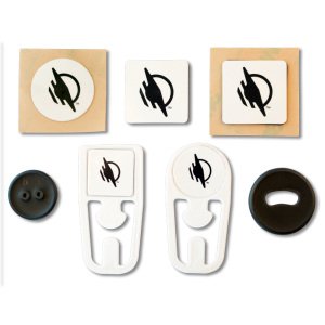Group of seven WayTags, including a round sticker, square magnet, square sticker, black 2 hole button, square top WayClip, round top WayClip, and black oval hole button.