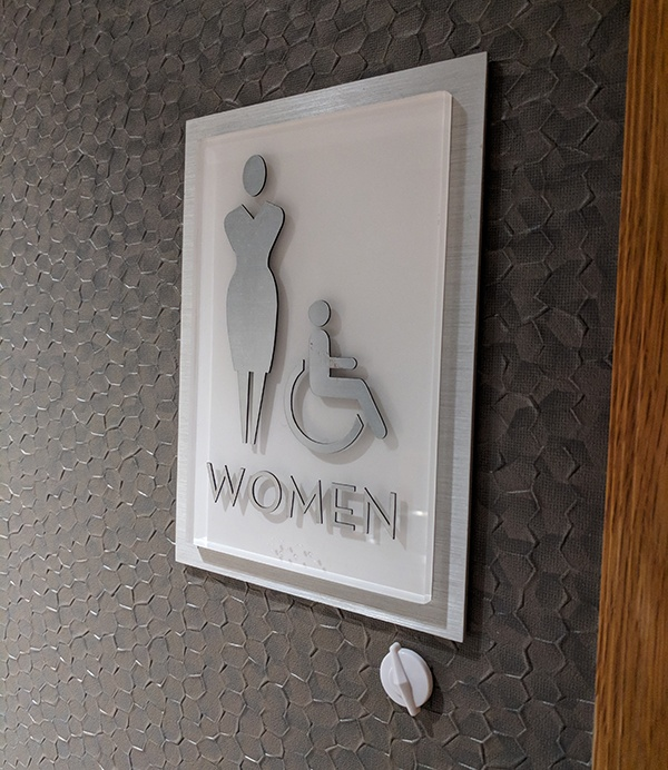 ADA sign for Women's Restroom with a 3D circular smart tag at the bottom right.