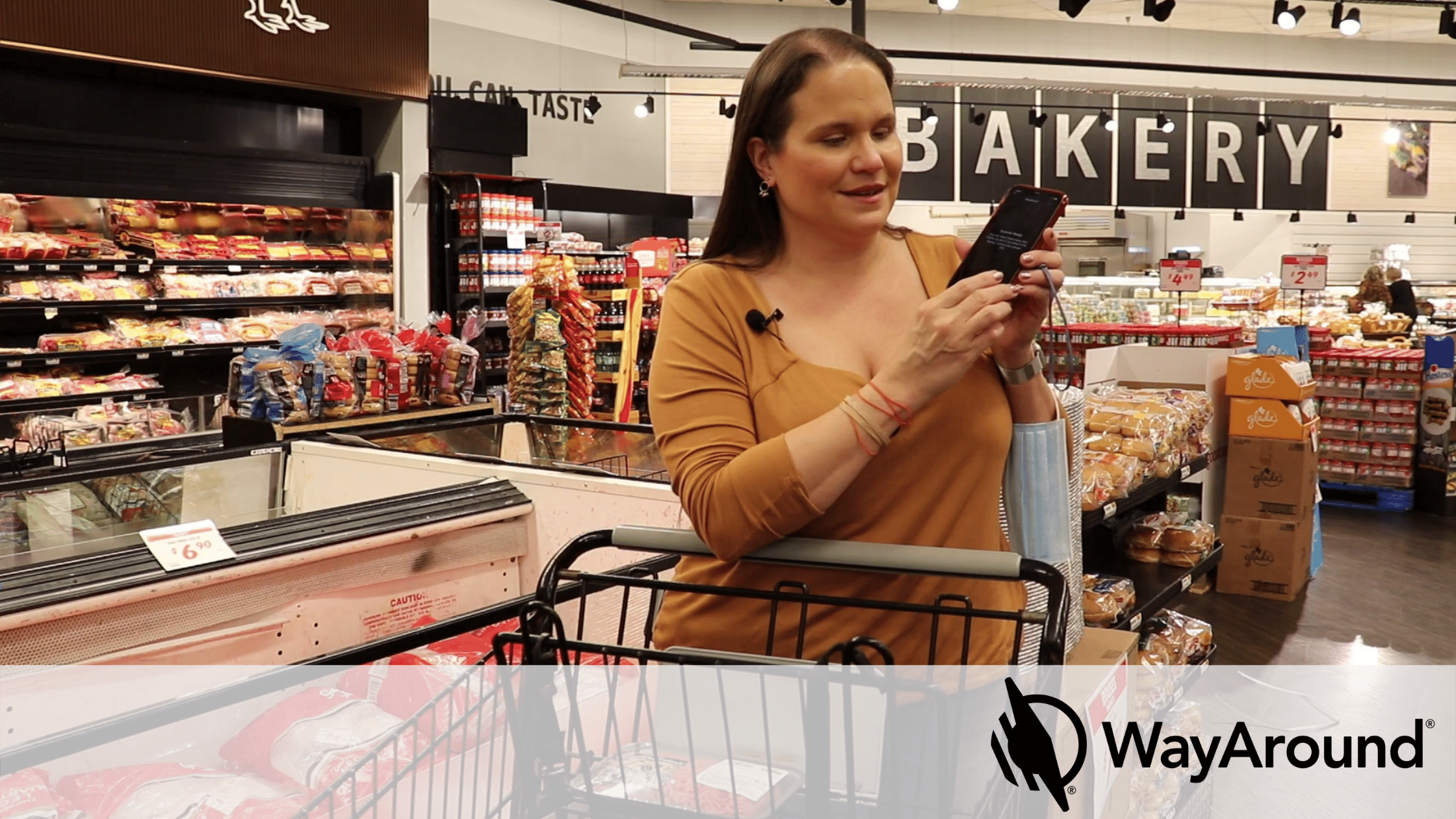 A woman leans on a shopping cart. She is looking at her phone. A sign in the background says Bakery.