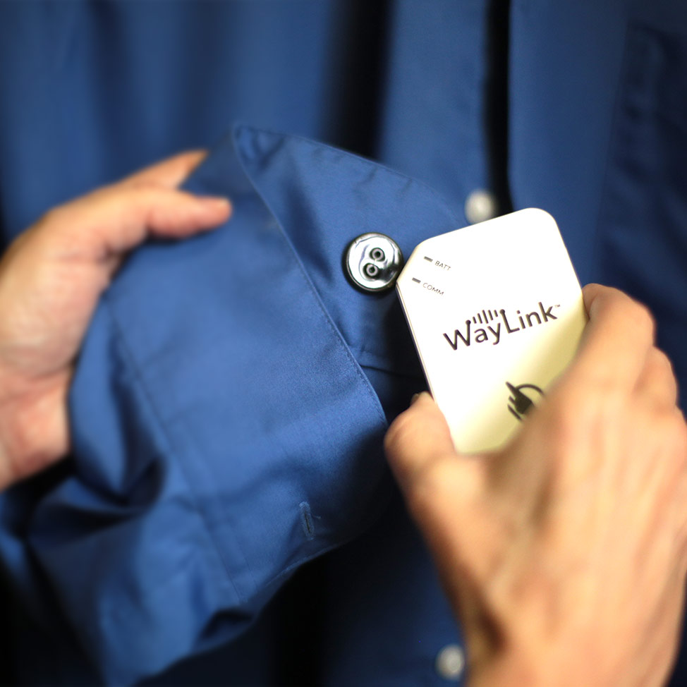 WayTag button sewn to the inside of a shirt sleeve being scanned using a WayLink device