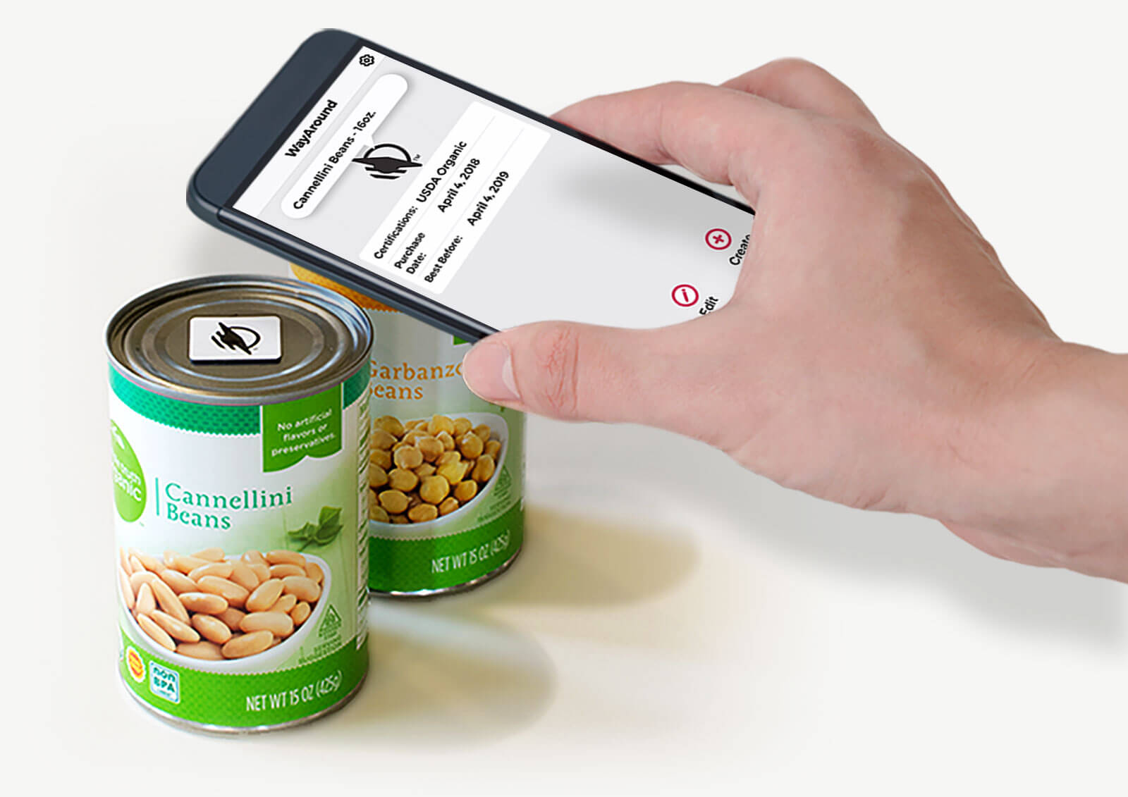 "Hand holding a smartphone just over a can of beans with a WayTag magnet visible on top of the can. The phone is showing the words ""Success, Tag Written"""