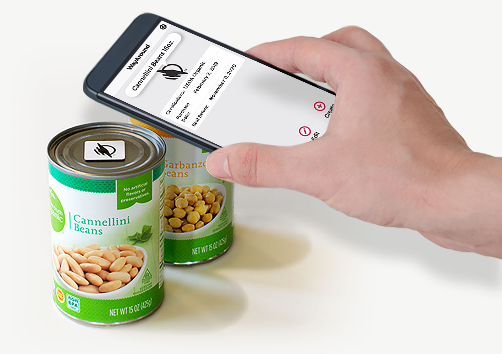 Hand holding a smartphone just over a can of beans with a WayTag magnet visible on top of the can. The phone shows the WayAround app with a description and product information for the cans of beans.