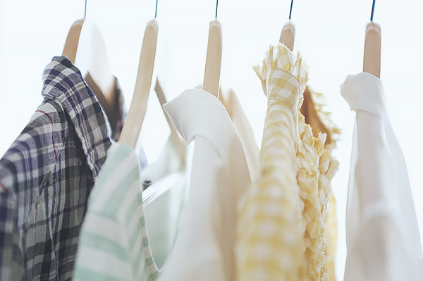 Five dress shirts with collars hanging on wooden hangers.