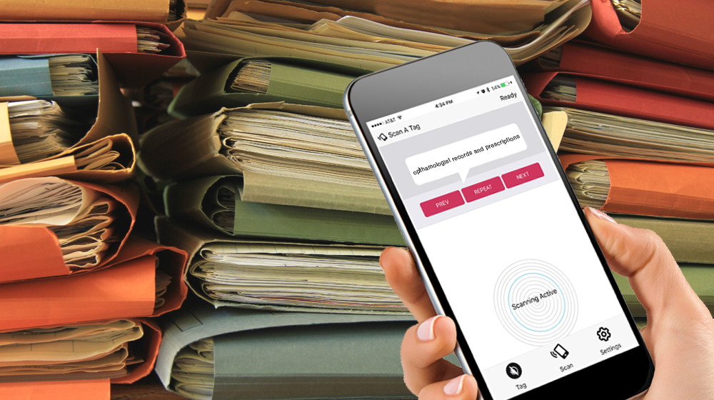 """Photo of a stack of multi-colored file folders and a person holding a smartphone. On the screen is the WayAround app with the text """"Opthamologist records and prescriptions"""""""
