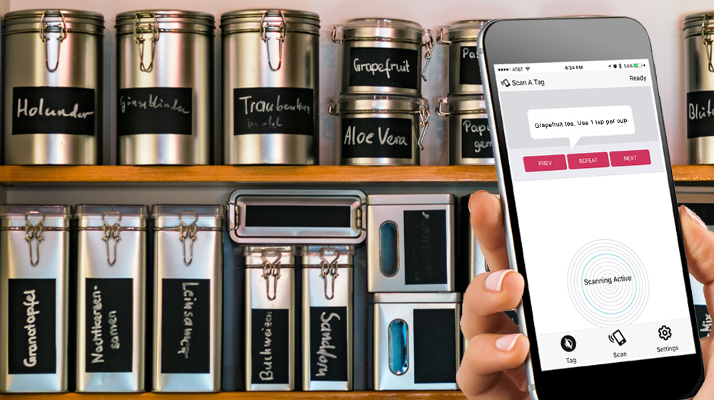"Photograph of kitchen shelves with various metal cannisters. Someone is holding a phone in front of the shelf. The WayAround app is on the screen with text that reads ""Grapefruit tea. Use 1 tsp per cup."""